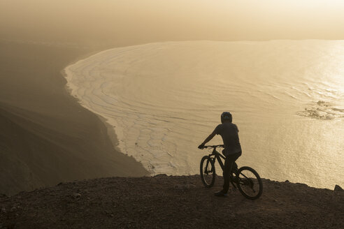 Spain, Lanzarote, mountainbiker on a trip at the coast at sunset enjoying the view - AHSF00105