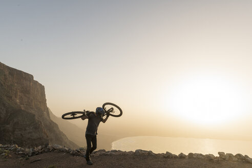 Spain, Lanzarote, mountainbiker on a trip at the coast at sunset carrying his bike - AHSF00108