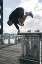 USA, New York, Brooklyn, young man doing Parkour handstand on railing of pier in front of Manhattan skyline - JUBF00337