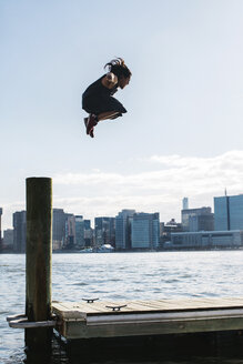 USA, New York, Brooklyn, young man doing Parkour jump from wooden pole in front of Manhattan skyline - JUBF00340