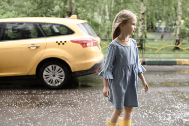 Girl wearing blue dress and vrossing road, yellow car in the background - EYAF00004
