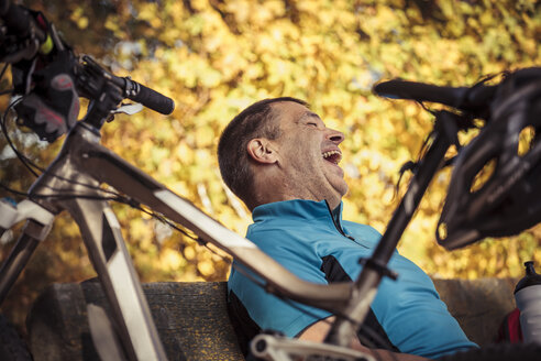 Laughing man with mountainbike having a break sitting on a bench - SEBF00060