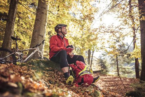 Man with mountainbike having a break in forest - SEBF00066