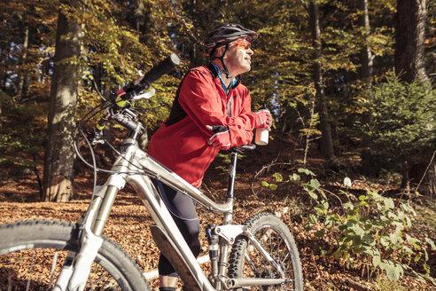 Man with mountainbike having a break in forest - SEBF00069