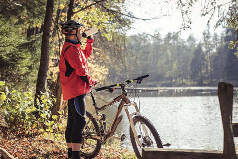 Man with mountainbike having a break at a lake in forest - SEBF00072