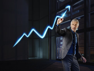 Businessman painting the stock market development with light - RORF01790