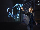Businessman painting a bull with light - RORF01793