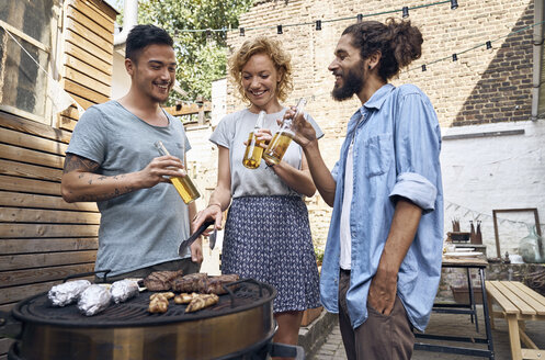 Friends having a barbecue n the backyard, preparing meat on a grill - PDF01818