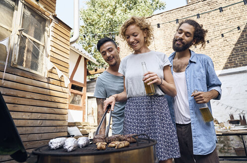 Friends having a barbecue n the backyard, preparing meat on a grill - PDF01821