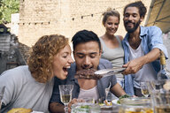 Friends having fun at a barbecue party, eating together - PDF01854