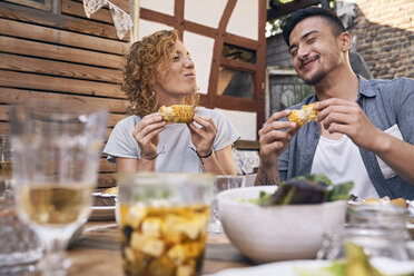 Couple eating grilled corn cobs at a backyard barbecue - PDF01857
