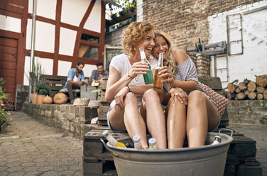 Friends relaxing in a backyard in summer, young women cooling their feet in a tub with drinks - PDF01860