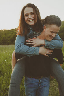 Young man giving his happy girlfriend a piggyback ride in nature - ANHF00093