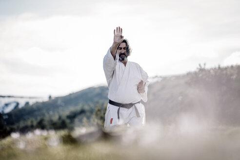 Senior man practicing karate outdoors - OCMF00306