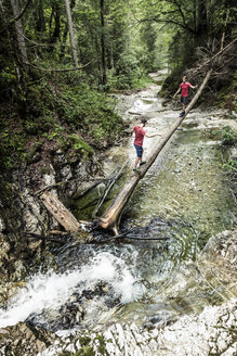 Germany, Bavaria, Upper Bavaria, lake Walchen, two young men are crossing a torrent on a tree trunk, twins - WFF00052