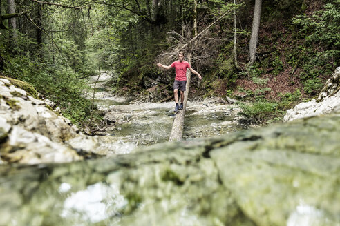 Germany, Bavaria, Upper Bavaria, lake Walchen, young man is crossing a torrent on a tree trunk - WFF00055