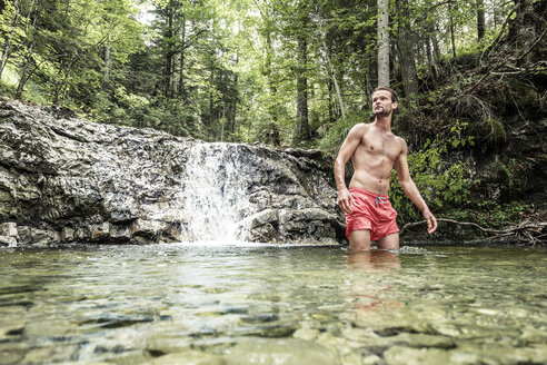 Germany, Upper Bavaria, Bavarian Prealps, lake Walchen, young man is standing in a torrent - WFF00061