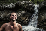 Germany, Upper Bavaria, Bavarian Prealps, lake Walchen, young man in a waterfall - WFF00067