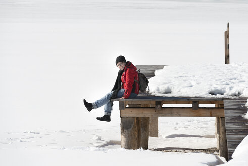 Austria, Tyrol, Achensee, woman sitting on jetty in winter - MKFF00455