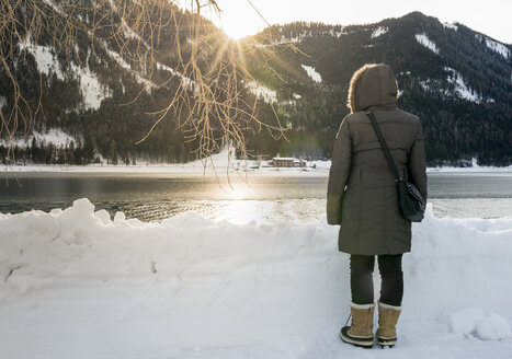 Austria, Tyrol, Achensee, woman standing at lake in winter at sunset - MKFF00464