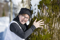 Portrait of smiling woman hugging a tree in winter - MKFF00470