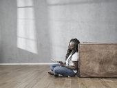 Woman sitting on the floor using digital tablet - FMKF05530