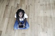 Portrait of smiling woman sitting on the floor with digital tablet - FMKF05533