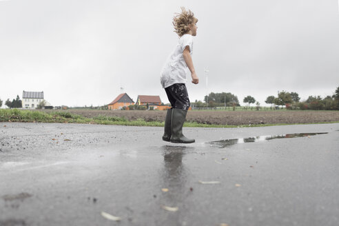 Boy jumping into a puddle - EYAF00018
