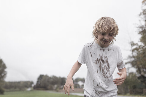 Portrait of blond boy with dirty face and t-shirt after jumping into a puddle - EYAF00021