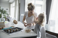 Daughter feeding cookie dough to mother baking in kitchen - HEROF30018
