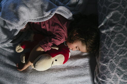 Toddler girl sleeping peacefully in bed  with a stuffed orangutan toy - GEMF02909
