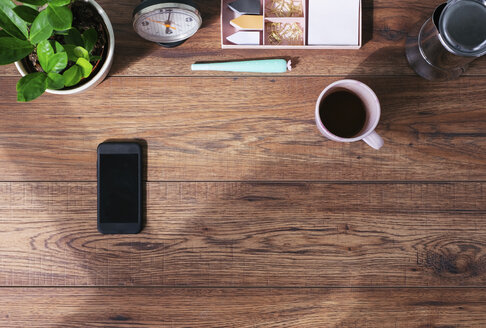 Wooden office desk with smartphone and coffee mug, top view - MOMF00638