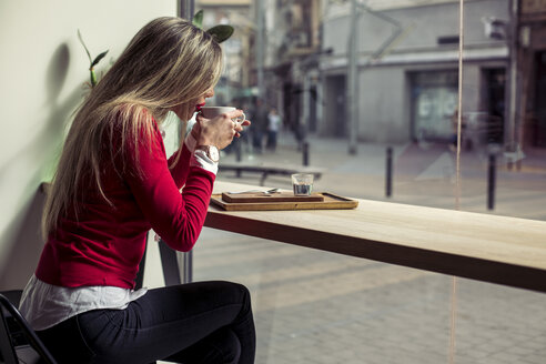 Woman sitting in a coffee shop drinking cup of coffee - ACPF00493