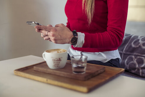 Woman using smartphone in a coffee shop, partial view - ACPF00496