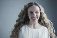 Portrait smiling Caucasian young woman with long curly blonde hair looking away - HEROF30083