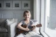 Portrait smiling girl playing ukulele at living room window - HEROF30101