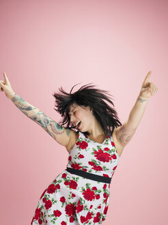 Exuberant young tattooed brunette woman dancing against pink background - HEROF30103