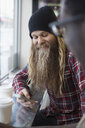 Hipster with long beard texting with cell phone in cafe - HEROF30124