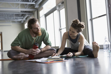 Man and woman on yoga mats writing in journal in gym studio - HEROF30127