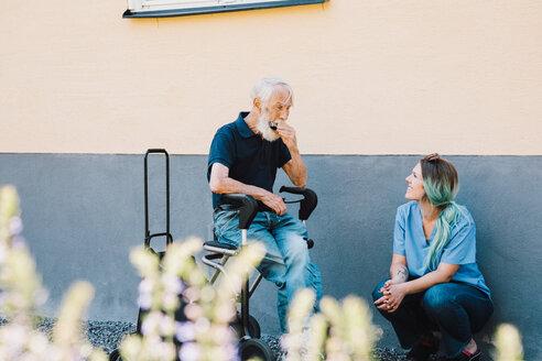 Smiling female nurse looking at senior man playing harmonica against wall at back yard - MASF11524