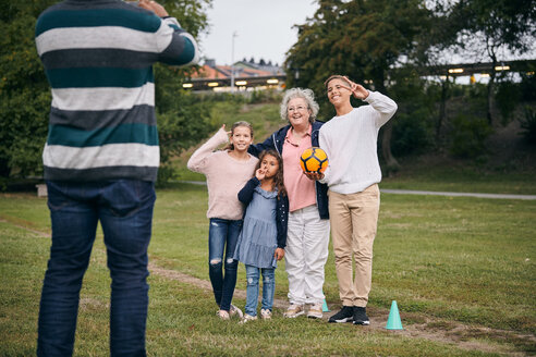 Midsection of man photographing happy grandmother and grandchildren gesturing peace sign in park during picnic - MASF11536