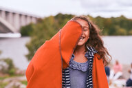 Cheerful girl with orange blanket enjoying in park during picnic - MASF11545