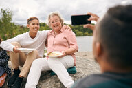 Man photographing grandson and grandmother with meal on rock during picnic - MASF11551
