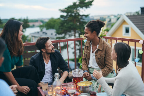 Happy friends talking while sitting on terrace during social gathering - MASF11563
