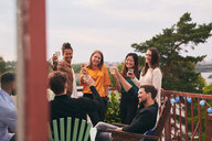 Happy friends toasting drinks on terrace during party - MASF11569