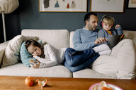 Girl using mobile phone while father showing digital tablet to sister on couch in living room at home - MASF11587