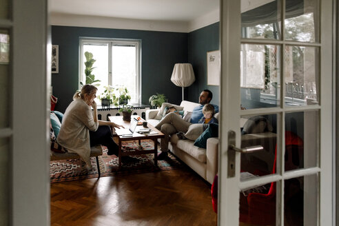 Family using various technologies in living room seen through doorway at home - MASF11590