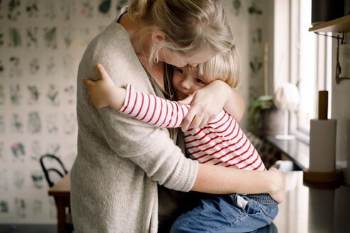 Loving daughter embracing mother while sitting on kitchen counter at home - MASF11593