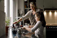 Daughter washing dishes while standing by mother in kitchen at home - MASF11602