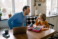 Playful father looking at daughter while using laptop at home - MASF11611